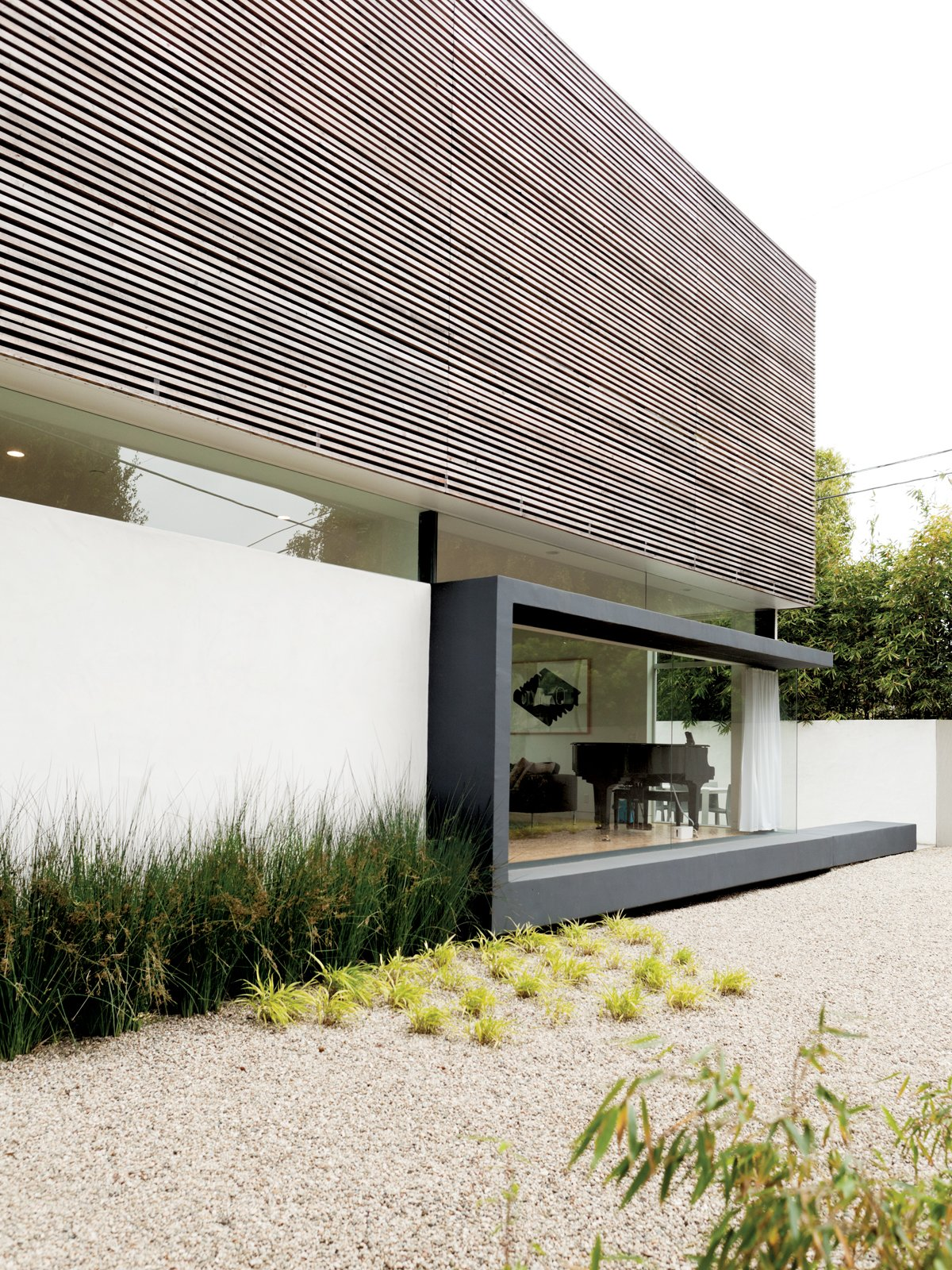 Exterior, House Building Type, Wood Siding Material, Stucco Siding Material, and Flat RoofLine The hardscaping helps keep water use to a minimum. The Lais used gravel—accented by drought-tolerant bamboo—to create their side yard.  Photo 5 of 13 in A Dream House for the Ages