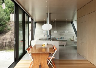 The concrete wall mimics the slope of the hill outside as a reference to early Maori structures that were dug into the land. The simple kitchen has strandboard cabinetry and an MDF island that conceals a fireplace at one end. The ceramic works on the built-in seat at right are by Raewyn Atkinson and Robyn Lewis.