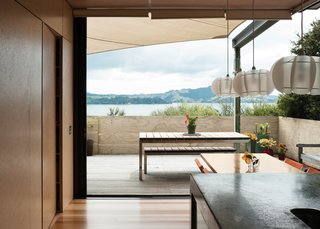 The north-facing doors slide completely away to open the house to the outdoors, offering an uninterrupted view of the water. The pendant lights over the table are from Iko Iko.