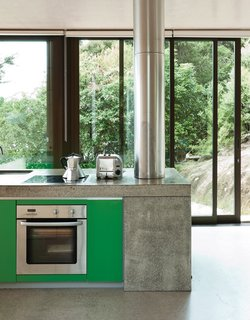 At a seaside New Zealand house, the simple kitchen has strandboard cabinetry and an MDF island that conceals a fireplace at one end. The bright green cabinetry of the island are a happy pop of color that references the native greenery outside.