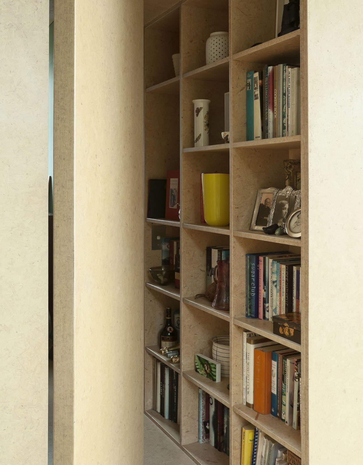 Yates used the same medium density fiberboard on this bookshelf as she did on the wall in the kitchen.  Photo 16 of 25 in Make Your Parents Happy by Building Them a House