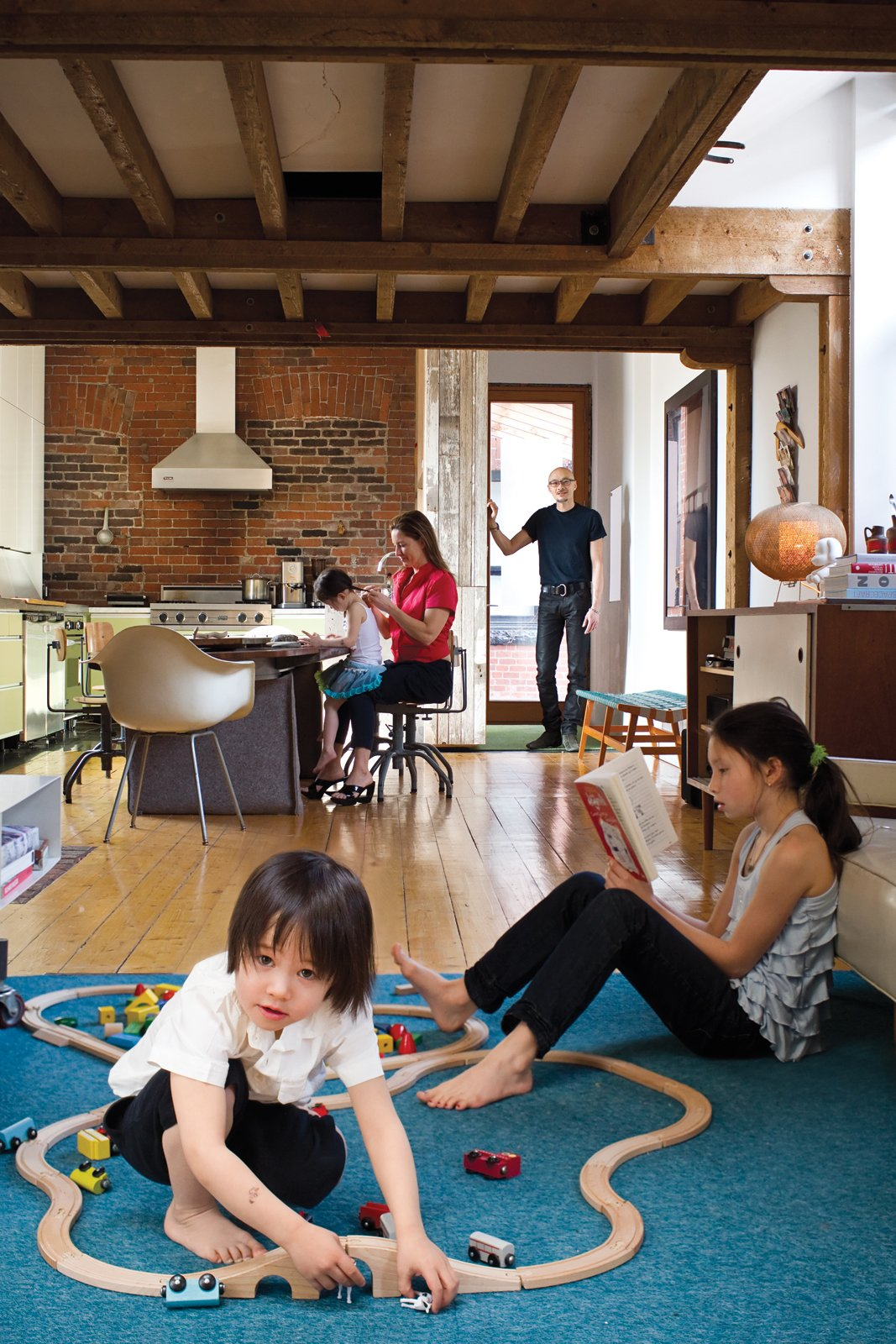Living Room and Light Hardwood Floor The house's open-plan layout encourages the entire family to hang out together, even while partaking in different activities. The durable area rug, made from carpet tiles by InterfaceFLOR, is the ideal base for both reading and playing with trains, as Luka, three, demonstrates.  Photo 4 of 13 in Play's the Thing
