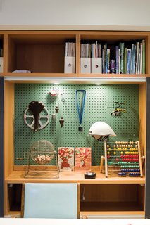 John built a shelf system for the basement when it was Anne's office; he adapted it to store the kids' toys when the area became a playroom.