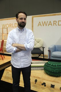 Designing the Modern World Award - Photo 1 of 2 - Dwell's Kyle Blue in front of the Modern World Awards exhibit at Dwell on Design.