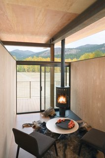 A compact interior with a black fireplace feels simultaneously cozy and boundless, with floor-to-ceiling glass doors that open out to views of the mountains of Washington state. The cork flooring, weathered steel, and wood walls contrast with the raised, open ceiling for the perfect mix of warm and minimalist, open and enclosed.