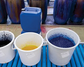 """The inks are stored in plastic wrap–covered buckets, which prevents a thick, top layer from forming. Each day, the color kitchen prepares hundreds of pounds of ink for the hues needed for the following day's printing. """"Thanks to having our own facilities, we can react quickly to sales,"""" Salmi says."""