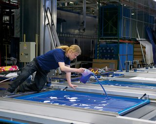 The printing machine moves fabric forward automatically, even though workers spread the inks across the plates by hand. No computers are needed to determine the right quantity.