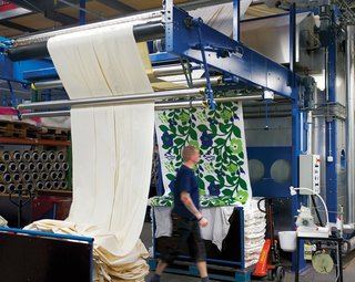 After printing, the fabric is transferred to the steaming machine, where steam heated to 219 degrees Fahrenheit fastens the color to the fabric, ensuring durability and brightness. Next, the textiles go through washing in 203-degree water to shrink them down to their final sizes. A finishing machine applies any additional treatments, like softener, to the washed fabric. Here, the colors of Katsuji Wakisaka's Green Green fabric are fastened to the cloth.