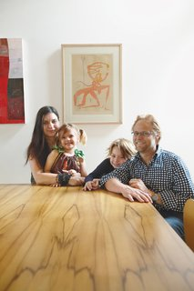 Wilkin and Pini, together with their children Ava and Tom, sit at a dining table made from black heart sassafras, an Australian wood.