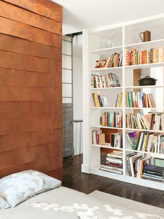 The copper-covered volume proceeds to the second floor, where it forms a storage wall in Sherman's home office.