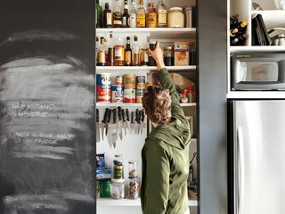 "Closet Case<br><br>To consolidate most appliances and food storage, keep his compact kitchen looking neat, and save money on cabinets, Sherman built a closet into the kitchen wall (""Cabinets are expensive but closets are cheap,"" he offers). Inside is a countertop, blackboard surface, toaster oven, garbage cans, magnetic knife rack, and plenty of shelves. When the doors are closed, the unit recedes from view."