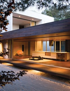 """Protected by an overhang, and floating above ground level, this tertiary space is known in traditional homes as the """"engawa."""" To sustain a unified look throughout, the floor and ceiling are clad in ipe wood."""