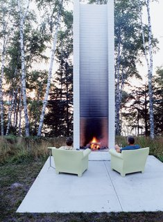 A dramatic departure from your typical cabin on the lake, this unique retreat adds shades of black to a tiny island awash with local color. A modern brick outdoor fireplace, tall and slim, is flanked by Philippe Starck's outdoor chairs for Kartell for cozy fireside seating.
