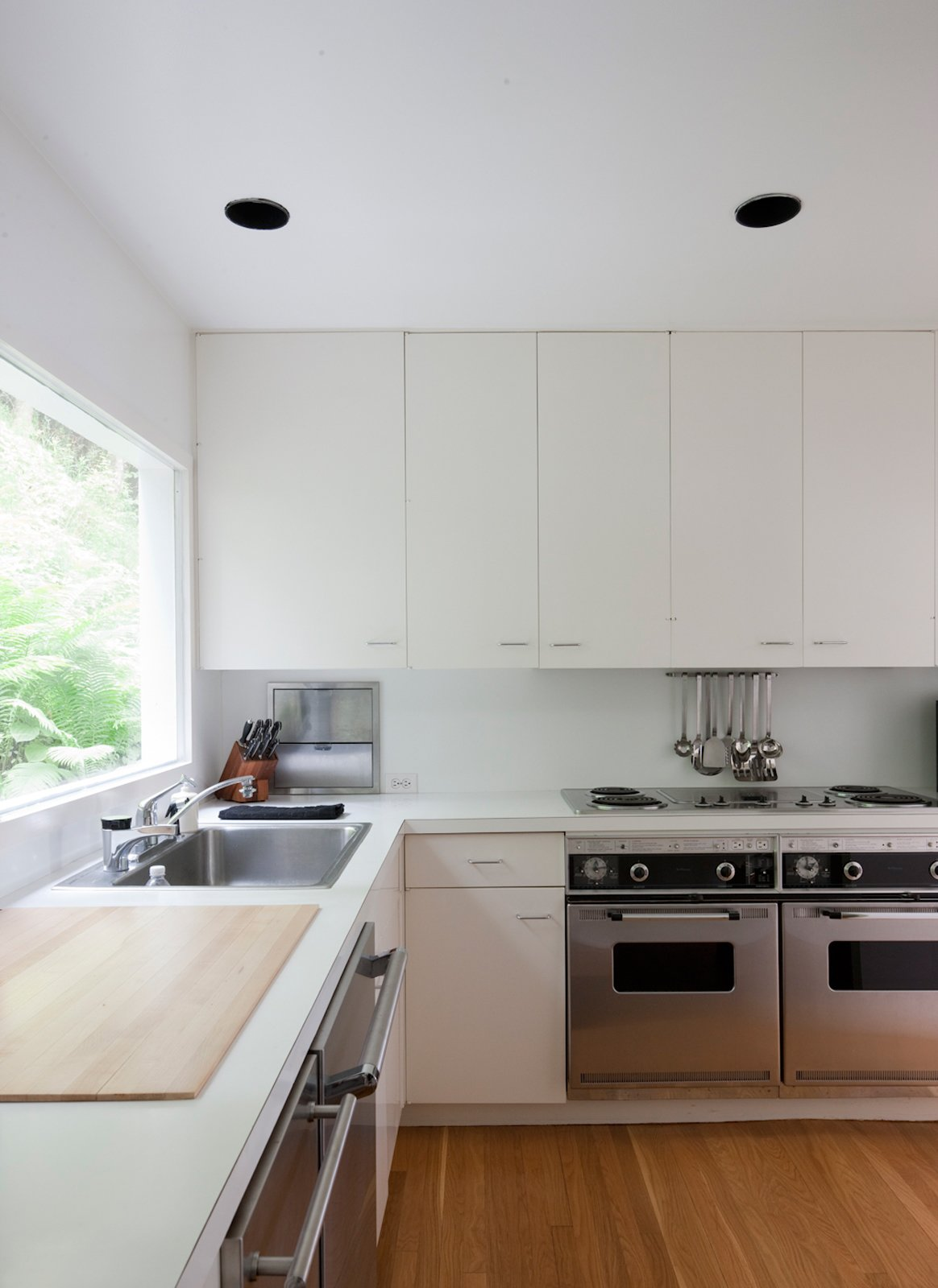 """The """"Meier white"""" extends even to the kitchen, which has been updated with new appliances.  Photo 19 of 22 in This Lake House Is a Living Piece of Architecture History"""