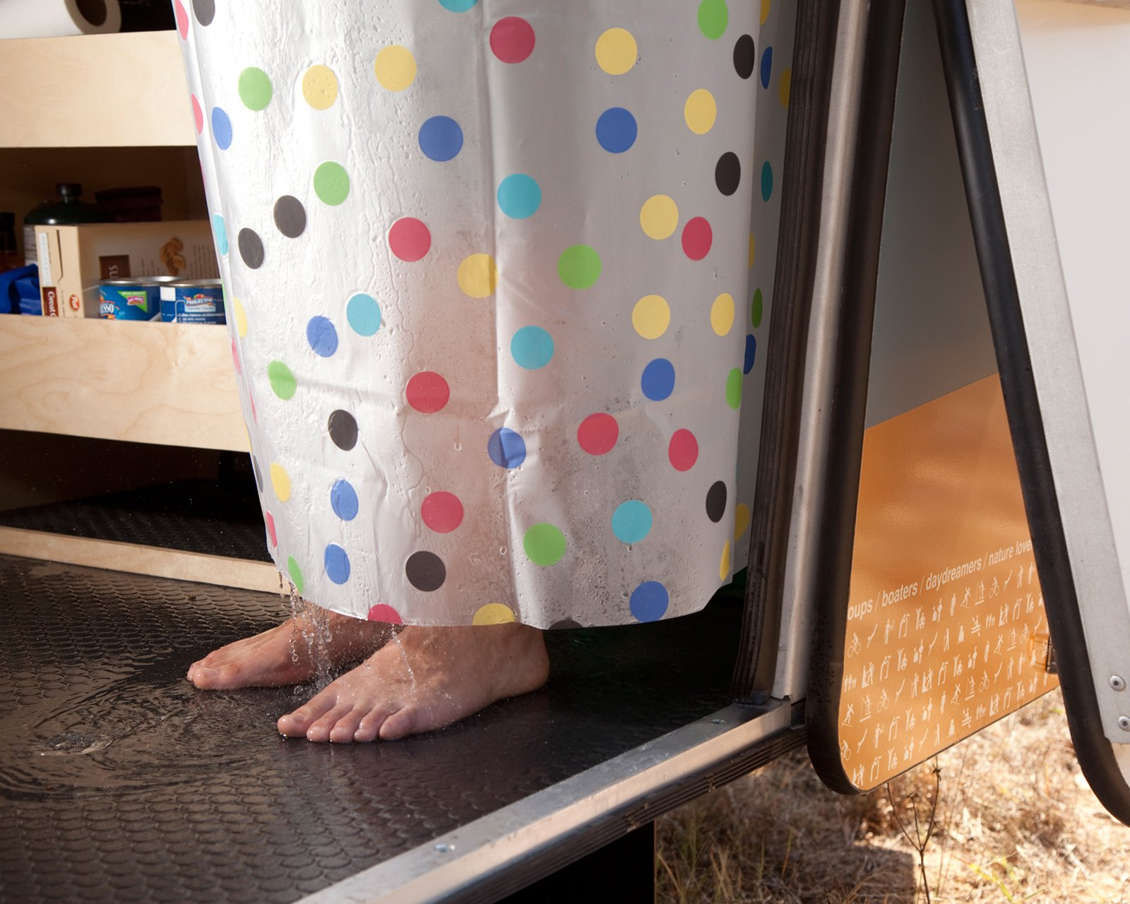 The handheld shower is intended for rinsing off muddy feet and pets rather than giving yourself a full-fledged scrub. Although you can use it inside the trailer (the shower curtain and floor drain will keep most of the water from splashing all over), it's best used when sprayed out the door.  Photo 6 of 15 in Modern NASA-Inspired Cricket Trailer
