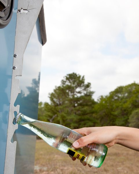 The front of the trailer features an aluminum bar laser cut with half of the word Taxa (the name of Cricket Trailer's parent company). The cutouts act as makeshift bottle openers. There is a learning curve, however; whereas Finney had no problem popping open cold Topo Chicos, I managed to spray myself with the carbonated water on more than one occasion.