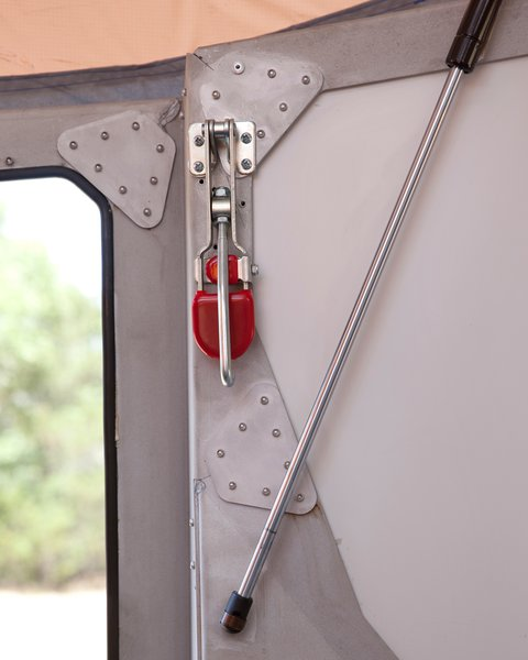 Hooks on the inside (like the mechanism with the red tab) latch into the camper's roof to help hold it down. Throughout the camper, small cricket images are laser-cut into the aluminum frame. The camper's name hints at its shape and is meant to conjure visions of sleeping under the stars with crickets chirping nearby.