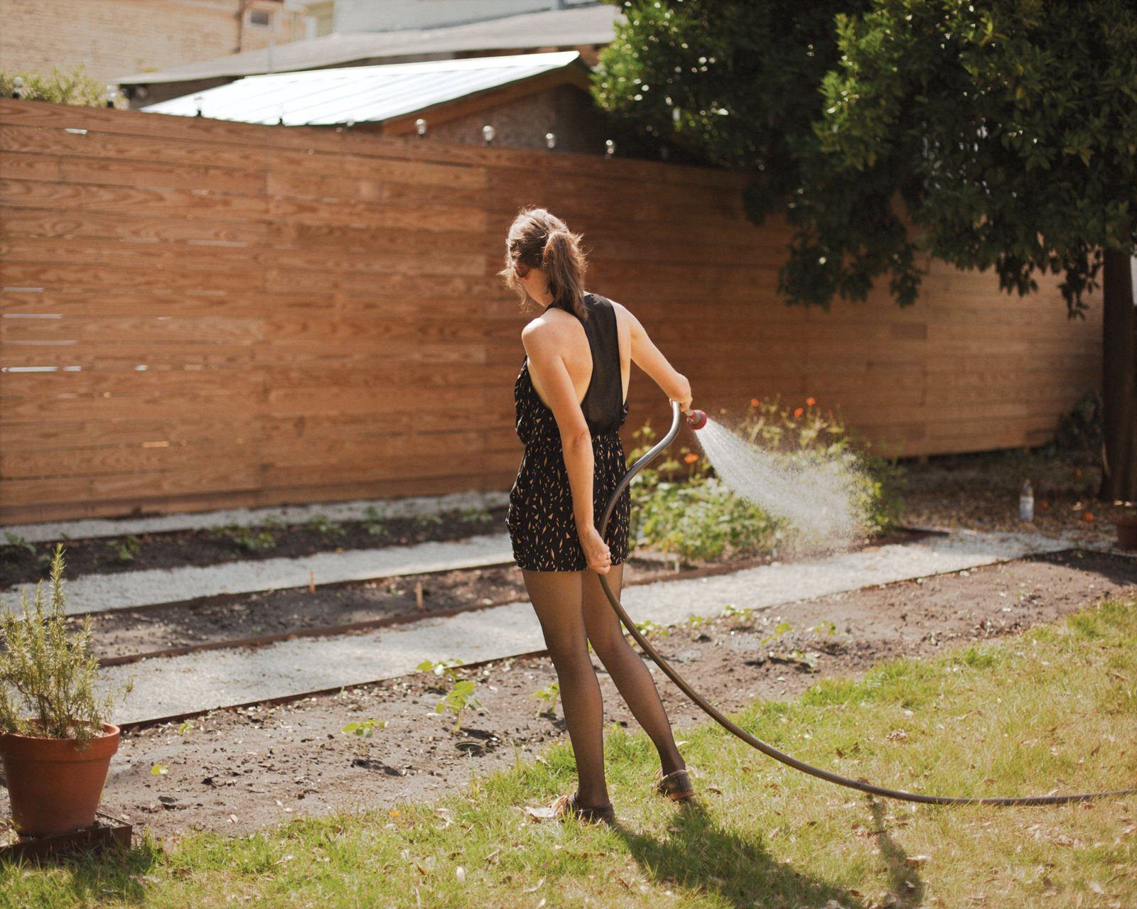 Helen Rice watering the garden outside of her Charleston residence.  Photo 12 of 18 in Raise High the Roof Beams