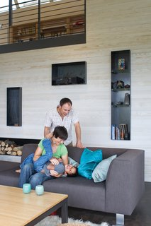 The open-plan living room and kitchen are a giant playground for five-year-old Suresh and his parents, as is the durable sofa and table base from Room & Board. Steel alcoves inset into the white-stained cedar wall shelter firewood, books, and treasured objects.