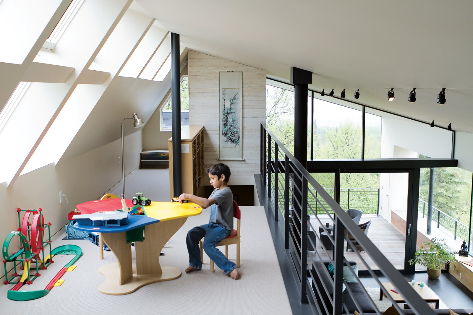 The loft above the living room is Suresh's terrain, given over to toys, books, and a colorful Lego table. The Clerestory windows maximize the natural light in the house—essential since there are only three hours of sun on a typical winter day.  Photo 3 of 10 in An Epic Plot
