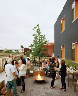 """Architect Douglas Stockman says the building's charcoal-and-orange exterior coloring was """"intended to reflect the dynamic character of the neighborhood."""" Here, it provides a festive backdrop to the residents' semi-annual Finn Lofts community party."""