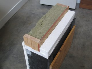 Our R-38 wall section. Rockwool insulation is placed in the 2x6 cavity, and 3.5 inches of continuous expanded polystyrene insulation is screwed to the outside of the oriented strand board shear wall. A benefit to this exterior insulation is that the thermally conductive bridge of the wood studs is broken by insulation. Even a thin layer of exterior insulation can make a big difference.