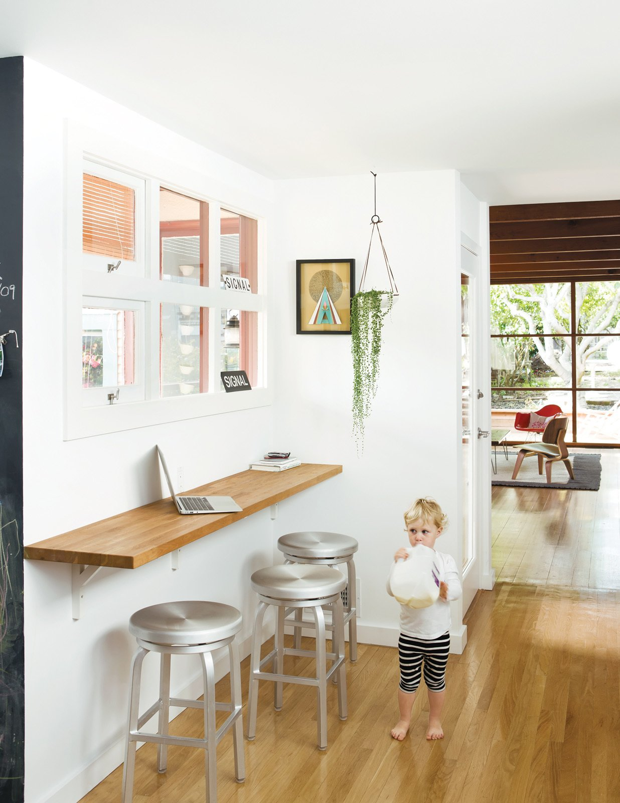 Dining Room, Bar, and Stools A wall-mounted oak bar is where Siminovich and Kerner drop their keys, pound away on their laptops, and occasionally eat a quick meal with Matilda, their two-year-old daughter.  Photo 7 of 10 in A Couple Tackles Conversion Challenges and Builds a Modern Renovation