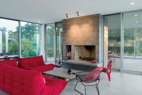 Floor-to-ceiling glass and sliding glass doors create a fluidity between indoors and outdoors, and frame views to the river beyond. The stone-and-brick fireplace acts as a nature-inspired anchor to the otherwise glazed living room.