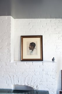 Revealing the Pros and Cons of Exposed Brick and How to Take Care of It - Photo 2 of 9 - Painted brick provides a textured backdrop for artwork, while still revealing historic features, like a brick fireplace.