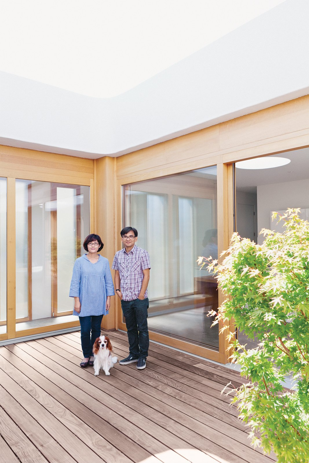 """Paul and Shoko stand on the ipe deck with their dog, Mei. """"At first, we really wanted an Eichler, but it just did not work out. But after seeing a few we knew we had to have a courtyard home,"""" says Paul.  Photo 2 of 19 in Looking Inward"""