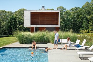 10 Coastal Prefabs That Bring Modular Housing to the Beach - Photo 8 of 10 - Green features such as a prefabricated foundation and a geothermal heating and cooling system are buried below the ground. Nontoxic finishes and passive systems inside the home add to its sustainable credentials and helped keep the project on budget. The result is an elegant beach house that's perfectly in tune with its environment. Here, the homeowners relax by the pool on modular furniture from Richard Schultz's Swell Seating Collection and chaise lounges from his 1966 collection for Knoll.
