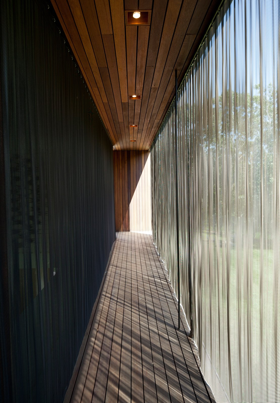 When extended, the metal-mesh curtain wall deflects the sunlight to mitigate the internal temperature of the structure. Similar energy-efficient gestures include geothermal heating and cooling, shading and venting systems, solar panels, and organic finishes and materials.  Photo 4 of 7 in Green Sustainable Home in Montauk