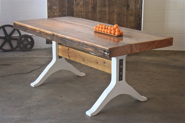 """One of McGowan's favorite pieces is this dining table. """"We found a 4.5-inch-thick old growth pine beam that was once used to support an 1800's building. We mounted it on white lacquered MDF legs to draw tension between the overly thick top and the glossy wishbone base,"""" he says."""