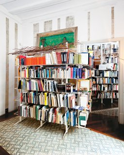 Freestanding shelving by Miralles holds yet more tomes from the family's prodigious collection. Irregularly placed tilework on the floor follows the trajectory of the sun's rays as it travels across the room.