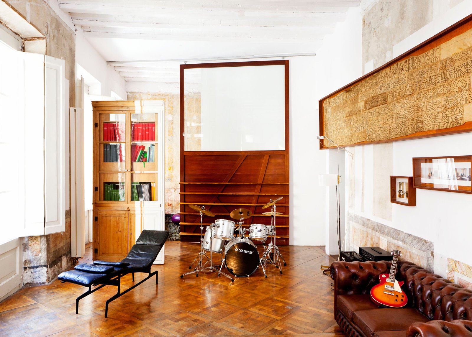 Living Room, Chair, Sofa, and Medium Hardwood Floor Sliding panels of Tagliabue's design delineate space in the first-floor sitting room, which opens to an office.  Photo 23 of 23 in The Barcelona Home Like No Other