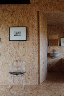A wire side chair by Harry Bertoia for Knoll sits outside the bathroom in the Stealth Barn.