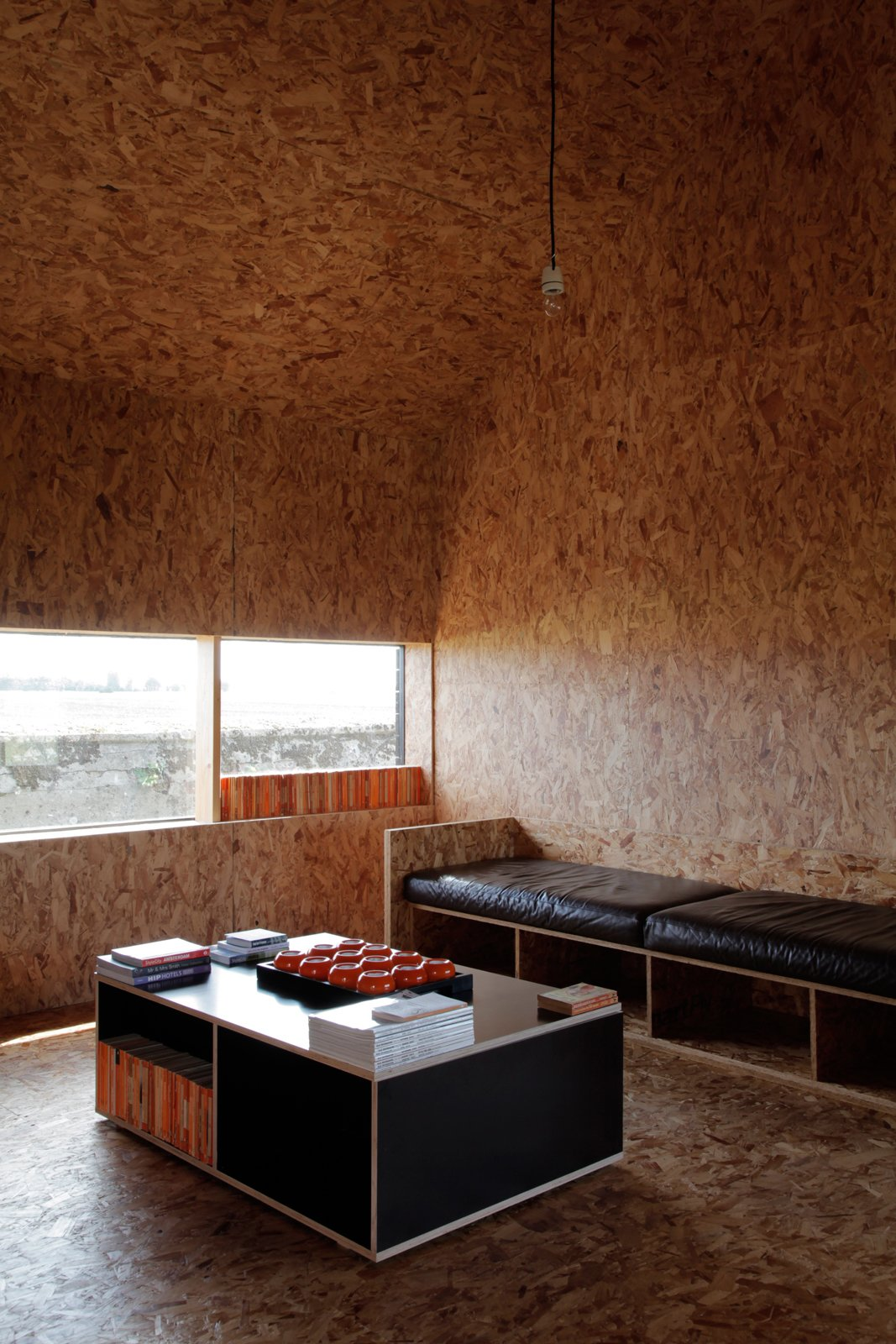 A row of Penguin Classics in the window casts an orange glow on the Stealth Barn's small OSB-clad living room outfitted with more custom furniture from Turner.  Photo 9 of 12 in A Pair of English Barns Hide Unabashedly Bold and Budget-Friendly Minimalist Interiors