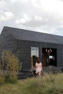 Carl Turner and Mary Martin pose on the porch of the Stealth Barn, a multipurpose structure that plays as a guest cottage, office space, and escape from whatever may be cooking at Ochre Barn.
