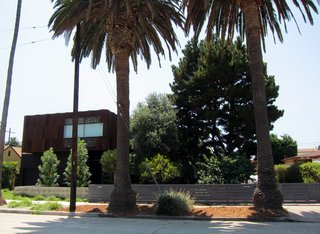 The street view of the property shows the dominance of trees at the front of the lot. The verge between the sidewalk and the curb features two large palm trees. Inside the property, a large pine tree is on the right and an oak tree on the left, in addition to some smaller fruit trees. The neighboring dwelling on the left, Walnut House by Modal Design, was featured in a 2010 Dwell on Design home tour.