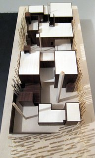 A wooden model of the house looking from the street front towards the rear alley. The house steps around major trees and offers numerous courtyards and rooftop gardens.