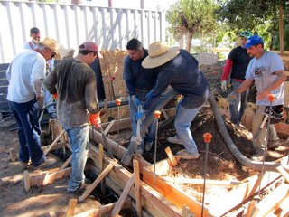 Concrete crew members work together during the pour as the hose is cumbersome to manage.