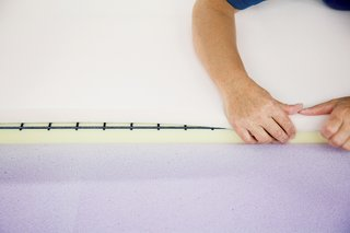 A technician sprays a sheet of pliable purple memory foam with a water-based adhesive and then carefully folds it over the other two foam layers and a steel spring grill to complete the backrest.