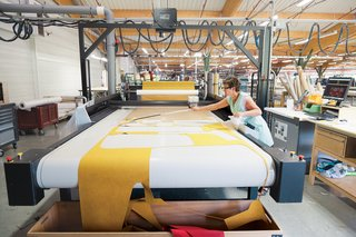 A seamstress mans the automated Gerber Cutter, which cuts patterns precisely and in a way that minimizes wasted fabric.