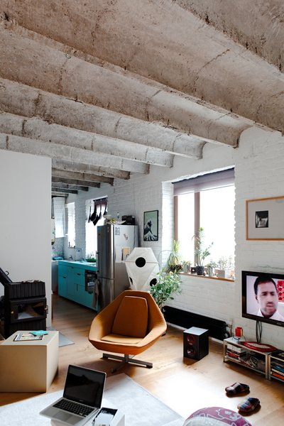 Here's a view from the bedroom toward the kitchen. Kordík knocked down a series of walls to open the space, but considerable light from the street and the clean white brick also help give it an expansive feel.