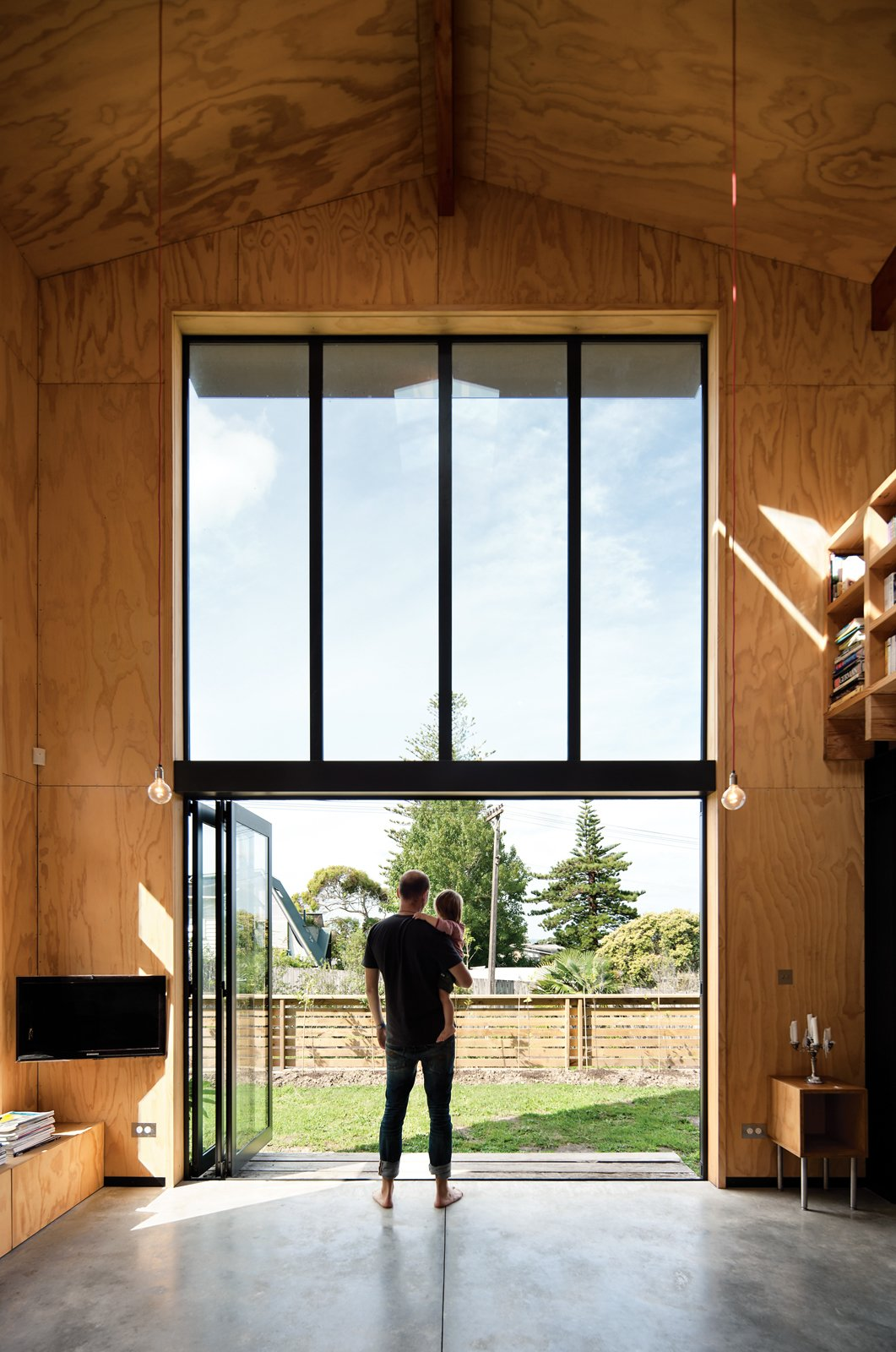 """Concrete Floor, Picture Window Type, Living Room, and Pendant Lighting Davor and August check out the yard from the living room. """"The bifold Vistalite doors allow us to open the house up completely and enjoy the fresh, warm air,"""" Davor says.  Photo 2 of 8 in Rock the Boat"""