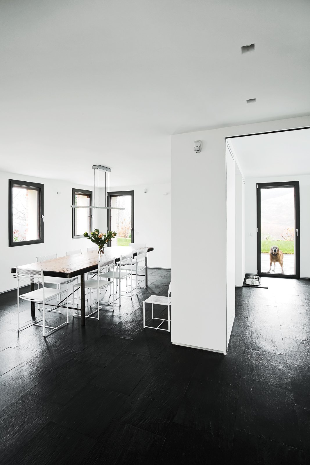 Dining Room, Dark Hardwood Floor, Table, and Chair In the dining area a vintage table from a shop in Barcelona is surrounded by Giandomenico Belotti Spaghetti chairs. The space, which also includes the kitchen, occupies a 1970s addition.  Photo 11 of 11 in 10 Exquisitely Modern Homes in Italy from A Renovated Farmhouse in Northern Italy