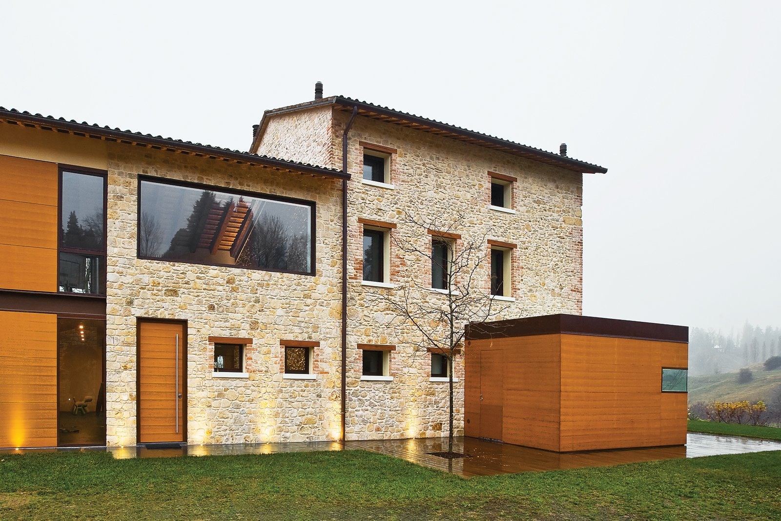 Exterior, Stone Siding Material, House Building Type, and Wood Siding Material Caprioglio paired the indigenous sandstone of the existing structure with teak mounted on   two-foot-wide panels. The structure at right holds the glass-topped kitchen.  Photo 11 of 13 in A Renovated Farmhouse in Northern Italy