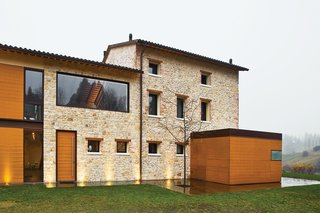 Caprioglio paired the indigenous sandstone of the existing structure with teak mounted on two-foot-wide panels. The structure at right holds the glass-topped kitchen.