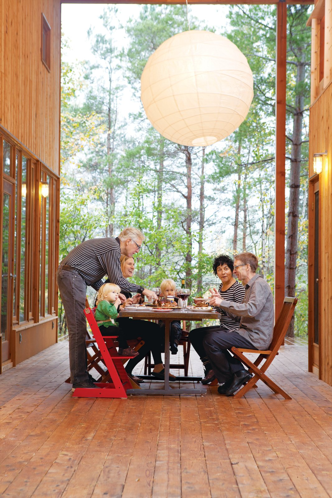 Dining Room, Chair, Table, and Pendant Lighting The large wraparound porch links the two main houses and two guest cabins, and is the site of many impromptu shared meals.  Photo 1 of 14 in Four Friends Joined Forces to Realize This Idyllic Forest Retreat Outside Toronto