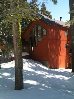 Snow in Bear Valley - Photo 2 of 4 - Amidst the brown natural tones of the surrounding cabins, this orange-red exterior pops. The contrasting charcoal trim and coordinated art in the window pull the whole thing together.